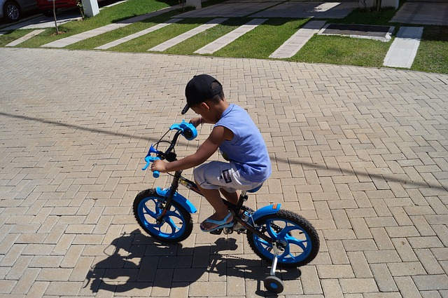 boy riding bike with stabilisers