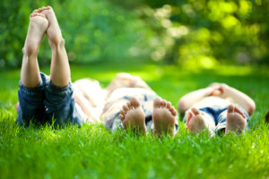 Group of happy children lying on green grass outdoors in spring park doing nature activities