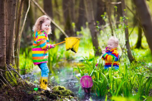 Children playing outdoors. Preschool kids catching frog with net. Boy and girl fishing in forest river. Adventure kindergarten day trip into wild nature, young explorer hiking and watching animals.