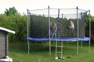 trampoline in a garden with children jumping on it